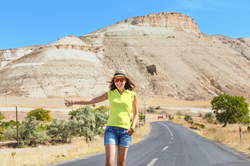 Woman hitchhiking on a road at the background of desert and mountains in Cappadocia