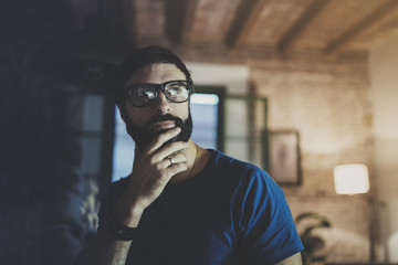 Closeup portrait of Handsome bearded man spending rest time at the modern home at evening.Horizontal. Blurred background.