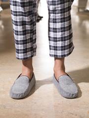 male feet wearing grey bedroom slippers on carpet.
