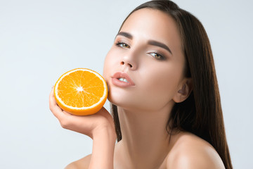 Beautiful woman's face with juicy orange