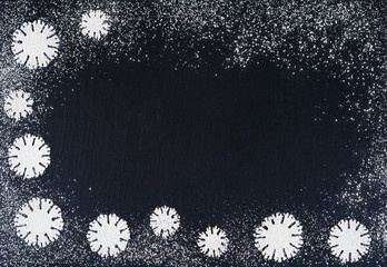 Creative winter snowflakes from powdered sugar background. Christmas and New Year backgrounds