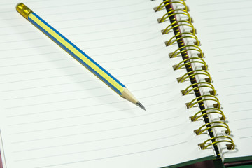sharp yellow pencil on spiral notebook and books