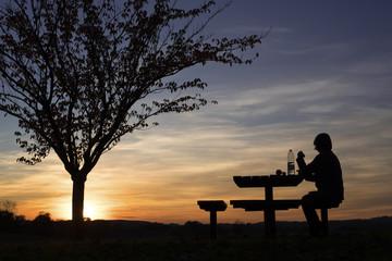 femme mangeant sur une aire de repos le soir