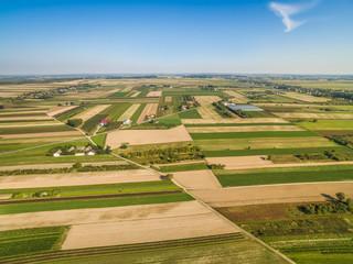 Krajobraz wiejski, z lotu ptaka. Droga przez pola uprawne. Pola uprawne, rozciągające się po horyzont.