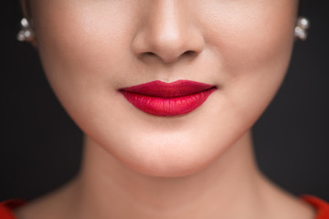 Beauty. Close up view of beautiful woman lips with red matt lipstick