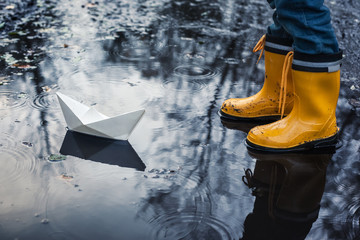 Child with Yellow Rain Boots and a little White Paper boat / Ship: Playing in a puddle, imagining his adventures