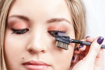 The final stage of makeup. The make-up artist combs the eyelashes of the model. Close-up