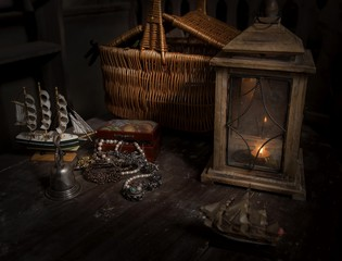 A model of sailboats, a trunk with decorations and a lantern with a basket.