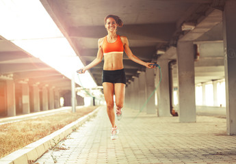 Female in sports wear workout with jump rope.
