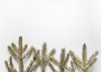 golden spruce branches lie like trees in a row at the bottom on a white wooden background