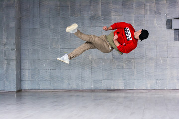 Young dancer in jumping. Modern style rap dancer in high jumping on grey background.