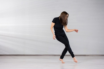 Girl dancer in movement. Young energetic girl in black suit dancing modern dance on studio background.