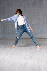 Modern young beautiful dancer in action. Beautiful young hip-hop dancer dancing contemporary urban street dance on studio background.