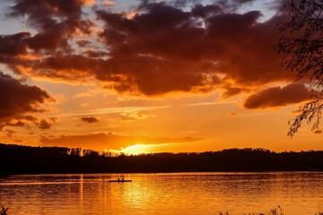 Photo sur Aluminium Rouge mauve Ruderer bei Sonnenuntergang am See
