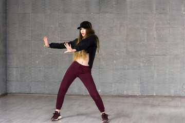 Pretty girl dancing modern dance. Beautiful slim young woman performing contemporary dance on studio background. Skillfull and talented youth.