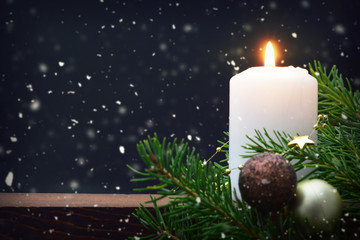 Christmas candle on dark snowy background