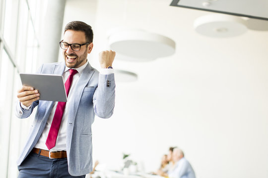 Happy businessman with tablet in office