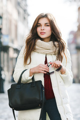 Outdoor portrait of young beautiful fashionable woman wearing stylish white winter puffer coat, holding leather tote bag, sunglasses. Model posing in street of european city. Female fashion concept