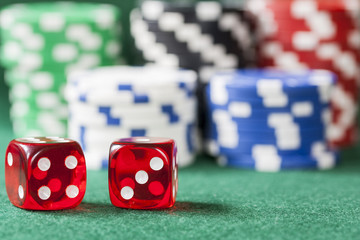 Stacks of gambling poker chips and pair of lucky seven dice on green felt