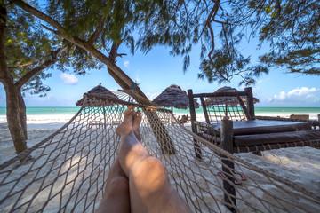 Man's crossed legs in hammock over tropical lagoon