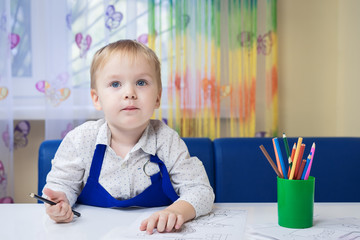 beautiful smiling caucasian boy 3 years old drawing with colored pencil in a notebook sitting at a desk in a classroom in a kindergarten (play room)