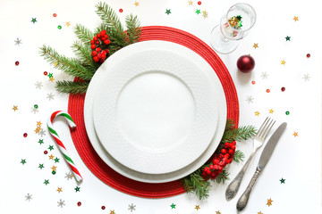 Christmas table setting with white dishware, silverware and red decorations on white background. Top view.