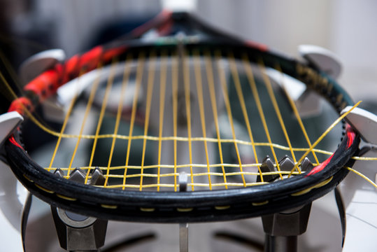 Stringing tennis racquet on professional electrical stringing machine
