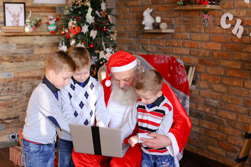 Close friends of children with Santa Claus use laptop in Christ