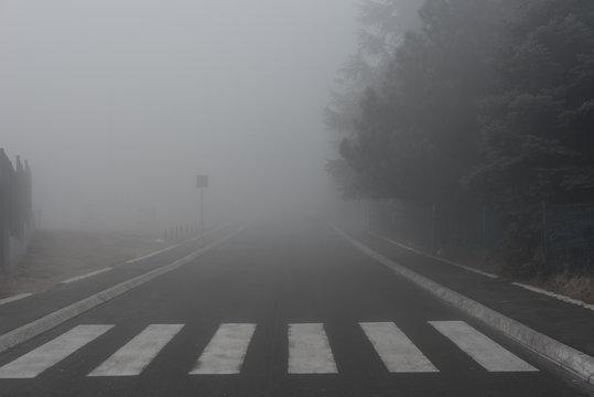 Pedestrian on empty street covered in fog