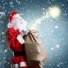 Weihnachtsmann mit Geschenkesack und Magie vor Winterhintergrund