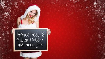 Weihnachtsfrau mit Kreidetafel vor rotem Weihnachtshintergrund