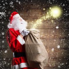 Weihnachtsmann mit Geschenkesack und Magie vor Holzhintergrund