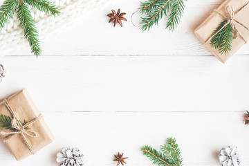 Christmas composition. Christmas gifts, fir tree branches, knitted blanket on white wooden background. Flat lay, top view, copy space
