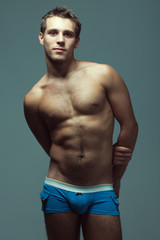 Male underwear fashion concept. Emotive portrait of young man in blue briefs posing with hands behind muscular body over blue background. Sportive style. Studio shot
