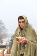 Young man tucked in green blanket outside, holding cup of steamy hot drink