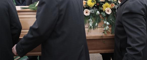 Sargträger tragen einen mit Blumen geschmückten Sarg