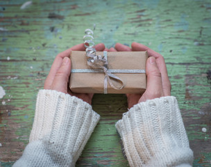 Female hands and gift box on rustic shabby wood background