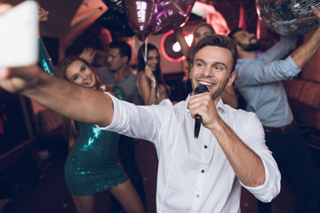 A man in a white shirt is singing in a nightclub. He has a microphone in his hands.