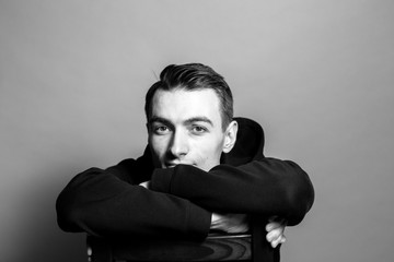 Black and white portrait of a young man in a black sweatshirt, sitting, head rests on hands, against plain studio background.