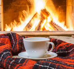 A cup of  tea,  woolen things near cozy fireplace, in country house, winter vacation, horizontal.