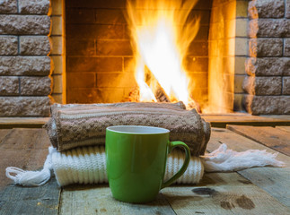 Mug  for tea or coffee,  wool things near cozy fireplace, in country house, winter vacation, horizontal.
