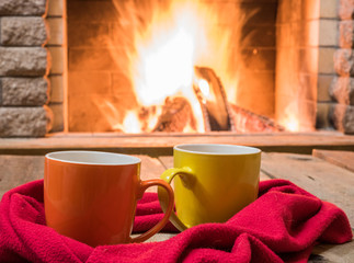Two  mugs  for tea,  wool things near cozy fireplace, in country house, winter vacation, horizontal.