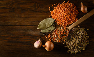 Red and green Lentils with spices on the wooden background.