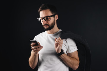 Bearded hipster wearing glasses and white blank tshirt looks on a smartphone. Young man standing in empty t-shirt on black background