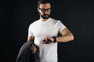 Bearded hipster in glasses wearing white blank tshirt holding a coat in hand and looks on smart watch on black background