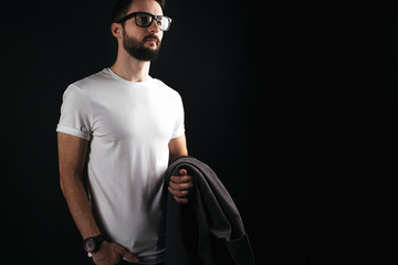 Beautiful bearded hipster in glasses stands in a white blanket tshirt in three-quarters on a black background