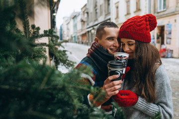 Young loving happy couple with coffee cups on the street in winter
