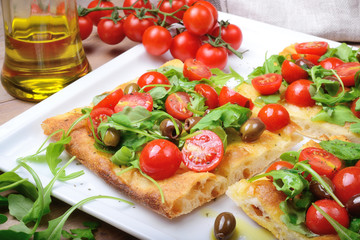 Focaccia with cherry tomatoes, arugula, olives and extra virgin olive oil