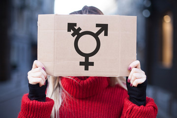 The symbol of the transgender in hands on a cardboard plate, covering (hiding) the face.