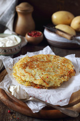 French cuisine. Pomme darphin: roasted pancakes from raw grated potatoes with sour cream